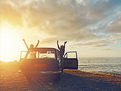 Auto parkt bei Sonnenuntergang am Meer. Zwei Menschen freuen sich mit hochgestreckten Armen.
