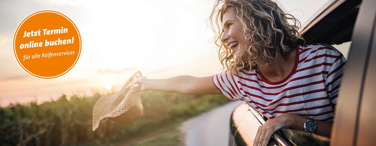 Frau lehnt sich aus dem Beifahrerfenster und hält einen Sonnenhut in der Hand.
